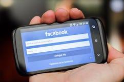WROCLAW POLEN - APRIL 05, 2014: Hållande smartphone för hand med Facebook den sociala nätverksmobilen app Royaltyfria Bilder