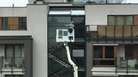 Wroclaw, Pologne - 25 avril 2019 : Le travailleur lave les fenêtres en dehors de la position de construction résidentielle sur la clips vidéos