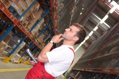 Wroker in warehouse. A man/worker with bar code reader rubbing his chin, deep in thought while standing in a warehouse royalty free stock photo