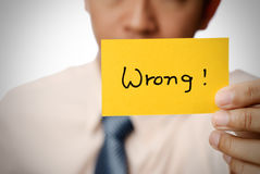 Wrong. Words on yellow card holding by businessman Royalty Free Stock Photography