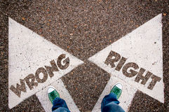 Wrong and right dilemma concept. With man legs from above standing on signs Stock Photo