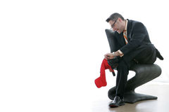 Wrong Use of Christmas Stocking. Man in suit puts Christmas stocking on foot. Plenty of white space for copy stock photos