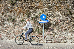 Wrong way. Businessman going on bicycle the wrong direction Stock Images