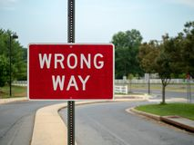 A wrong way red sign at a local neighborhood driveway with space to the right royalty free stock photography