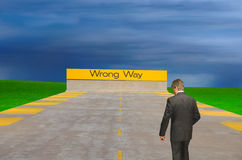 Wrong way sign with confused lost man Stock Photos