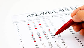Wrong way to answer. Hand holding red pen for making marks on answer sheet represent using wrong equipment on exam royalty free stock photography