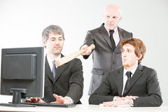 Wrong ways of managing a teamwork. Boss pointing out to something on the screen with a baseball bat and frightening two generation of office workers Stock Photos