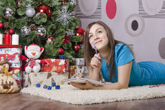 She wrote a letter to Santa Claus, lying near the Christmas tree Stock Photo