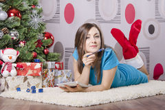 She wrote a letter to Santa Claus, lying near the Christmas tree Stock Photos