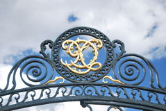 Wrought emblem. On a metal fence over a cloudy sky Royalty Free Stock Photography