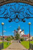 The wrought-iron arch above the entrance to the alley and the beautiful church in the background. For your design Stock Images