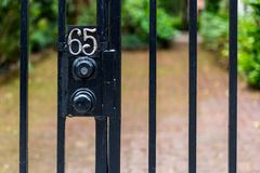 Entrance Number 65. Wrought Iron bars, a gate, and a deadbolt lock protect what`s behind the number sixty five Stock Photography