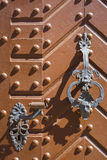 Wrought-iron bell and handle on orange door with metal rivets Stock Photos