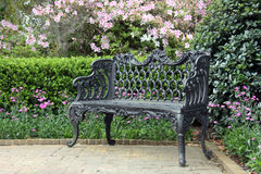 Wrought iron bench. With a flower garden background Royalty Free Stock Images