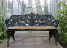 Wrought iron bench in garden Stock Images