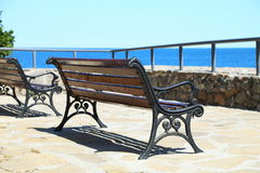 Wrought-iron bench on a stone seafront. Stock Photography
