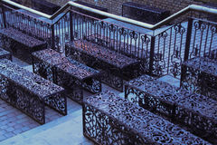 Wrought iron benches in Camden Market. At dusk. Light reflecting on the benches from food stalls Stock Image