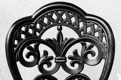 Wrought Iron Chair Back in Black and White. Close up of a wrought iron chair against a stucco wall in black and white Stock Photo