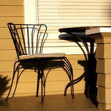 Wrought Iron Chair on Porch. A wrought Iron bistro chair is seen on the porch of a yellow home Stock Photo