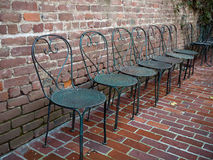 Wrought iron chairs lined up on a brick patio Stock Image