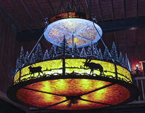 A Wrought Iron Chandelier Hangs in a Forest Lodge Royalty Free Stock Image