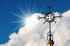 Wrought Iron Cross - Religious symbol. Wrought iron cross on a blue sky with clouds and sun rays, Christian religious symbol. Church of the Sacred Heart in La royalty free stock image