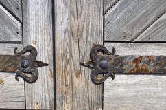 Wrought iron door hinge on old wooden background Stock Photography