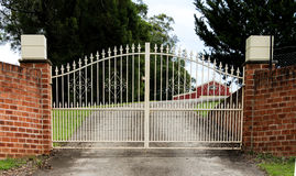 Wrought iron driveway entrance gates set in brick fence. Wrought iron metal driveway entrance gates set in brick fence Royalty Free Stock Images