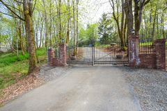 Wrought iron driveway gates with red brick columns. Wrought iron driveway gates with red brick columns leading to a beautiful secluded home. Northwest, USA Stock Images