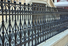 Wrought iron fence. Close up look of wrought iron fence in front of the modern building Stock Image