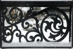 Wrought iron fence creates interesting pattern in snow. Patterns in dark black iron fence contrasts dramatically against snowy background on a wintry winter day royalty free stock image