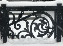 Wrought iron fence creates interesting pattern in snow. Patterns in dark black iron fence contrasts dramatically against snowy background on a wintry winter day stock photos