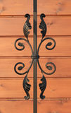 Wrought-iron fence elements of railing on wooden background Royalty Free Stock Photos