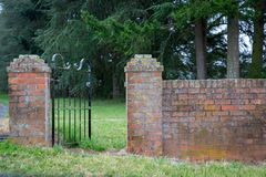 A wrought iron fence gives entry through an old brick fence stock image