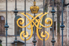 Wrought iron fence with monogram. Wrought iron fence with a gilded monogram. Alexeevsky Palace, St. Petersburg, Russia Stock Images