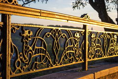 Wrought iron fencing with mythical creature. Decorative lattice in shape of Simargl, mythical creature, winged lion or dog. Photo taken in historical part of Royalty Free Stock Photography