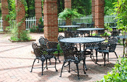 Wrought Iron Furniture in Airy Courtyard. A sunlit courtyard is the setting for relaxation with outdoor ornate wrought iron chairs and tables. Vines climb the Royalty Free Stock Photography