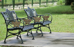 Wrought Iron Garden Benches. That were bolted to concrete slab in the field stock image