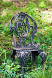 Wrought Iron Garden Chair in the Woods Stock Photo