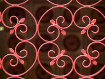 Wrought Iron Gate. Kidney-shaped elements with double inward spirals at its ends repeated used as a design element in a vermiiion coloured wrought iron gate stock photo
