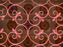Wrought Iron Gate. Kidney-shaped elements with double inward spirals at its ends repeated used as a design element in a vermiiion coloured wrought iron gate. A royalty free stock image