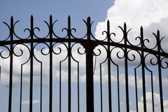 Wrought-iron Gate. A wrought-iron gate against the blue sky with some clouds royalty free stock photo