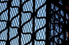 Wrought iron gate in backlight, blue sky behind Royalty Free Stock Photos