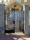 Wrought Iron Gate. A black wrought iron gate, partly opened with the sun shining through it leading to stairs up to a houses front door Royalty Free Stock Images
