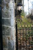 Wrought Iron Gate Fence and Lamp. Old world style gate with lit lamp from an old english garden. Wrought Iron Fencing is seen an white stone wall in front of a Stock Images