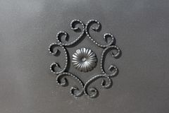 Wrought iron gate ornament on grey metal plate Royalty Free Stock Image