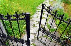Wrought iron gate, garden stone path. A photograph showing the details of an low antique style wrought iron gate of a pretty French garden, and the irregular Stock Photography