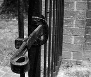 Wrought Iron gate with latch near brick wall Royalty Free Stock Image