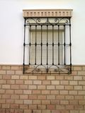 Window with security grill. Wrought Iron grill over window with Grecian frieze lintel Royalty Free Stock Image
