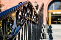 Detail of Wrought Iron Handrail. A wrought iron handrail running along a set of steps outside of a brick building entrance stock photography